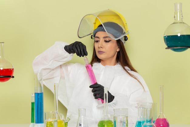 녹색 벽 화학 실험실 화학 직업 여성 과학에 솔루션을 사용하는 특수 보호 복에 전면보기 젊은 여성 화학자