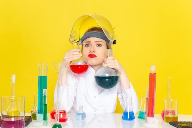 Вид спереди молодая женщина-химик в белом костюме, держащая различные решения на желтом космическом химическом науке