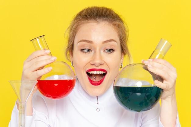 Вид спереди молодая женщина-химик в белом костюме, держащая разные растворы на желтом космическом химии