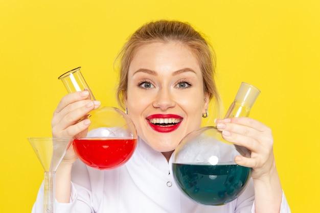 黄色の宇宙化学の仕事に笑みを浮かべてさまざまなソリューションを保持している白いスーツで正面の若い女性化学者