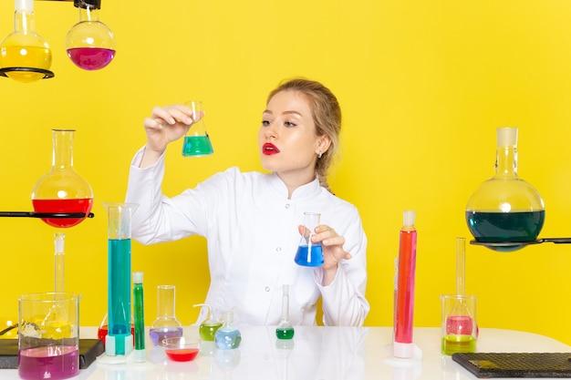 正面図の若い女性の化学者、テーブルの前に白いスーツで、黄色の宇宙化学科学実験に1つを保持しているedソリューション