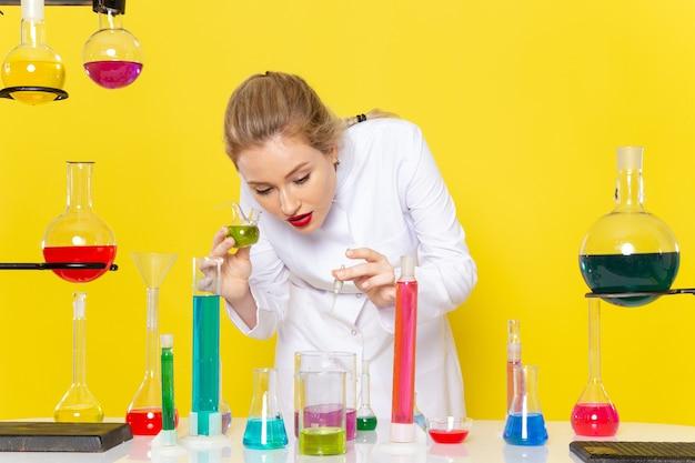 正面の若い女性の化学者、黄色の空間化学科学実験のedソリューションとテーブルの前に白いスーツ