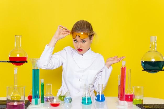正面から見た若い女性の化学者、テーブルの前に白いスーツで、edソリューションが黄色の宇宙化学の仕事でそれらを扱う