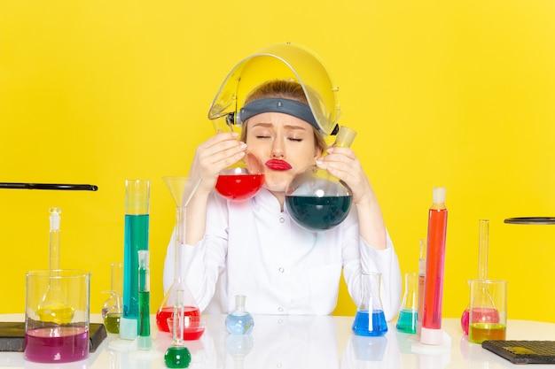 노란색 공간 화학 과학의 프로세스 작업에 다른 솔루션을 앉아서 들고 흰색 정장에 전면보기 젊은 여성 화학자