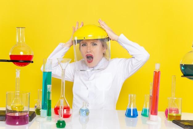 Вид спереди молодая женщина-химик в белом костюме с решениями ed в шлеме на желтой космической химии