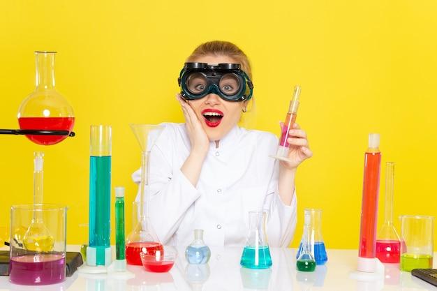 正面から見たedソリューションと白いスーツの若い女性化学者と協力して、黄色の宇宙化学科学に笑顔で座っています。