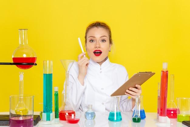 黄色の宇宙化学科学sにメモ帳を保持しているそれらと一緒に働いているedソリューションと白いスーツの正面の若い女性化学者