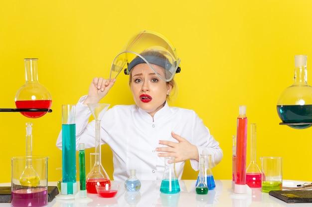 Вид спереди молодая женщина-химик в белом костюме с ed-растворами, работающая с ними в шлеме на желтой космической химии