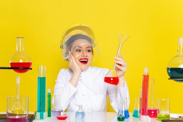 正面から見た若い女性の化学者、白いスーツを着て、黄色の宇宙化学科学のプロセスにヘルメットをかぶってそれらと一緒に働くedソリューション