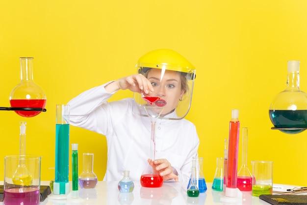Вид спереди молодая женщина-химик в белом костюме с решениями ed, работающими с ними в шлеме на желтом космическом химическом процессе