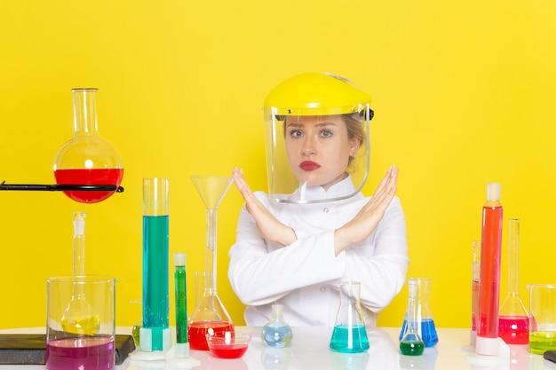 正面から見た若い女性化学者、白いスーツを着て、黄色の宇宙化学科学のプロセスでヘルメットをかぶってそれらを扱うedソリューション