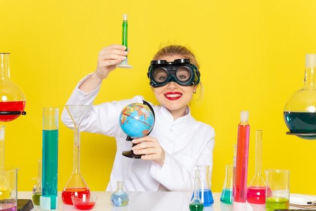 Вид спереди молодая женщина-химик в белом костюме с растворами ed, работающими с ними в маске, улыбается на желтом космическом химии