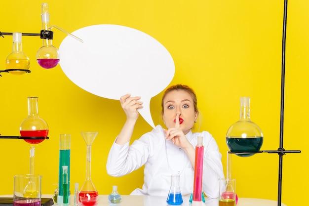 노란색 바닥 화학 과학 과정에 흰색 기호를 들고 다른 솔루션과 흰색 정장에 앉아 전면보기 젊은 여성 화학자