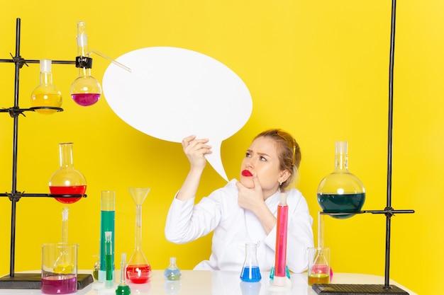 노란색 공간 화학 과학 과정 작업에 흰색 기호를 들고 다른 솔루션과 흰색 정장에 앉아 전면보기 젊은 여성 화학자