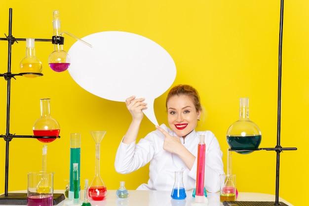 노란색 바닥 화학 과학에 웃는 흰색 기호를 들고 다른 솔루션과 흰색 정장에 앉아 전면보기 젊은 여성 화학자