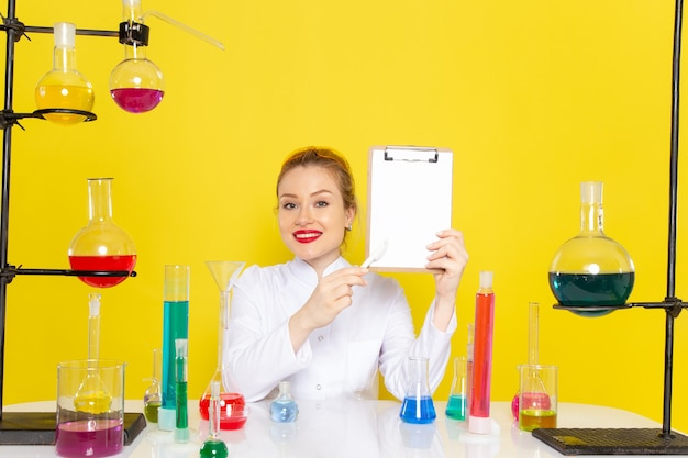 Front view young female chemist sitting in white suit with different solutions holding notepad and smiling on the yellow space chemistry science  process job