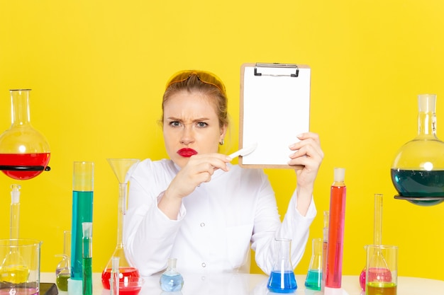 Front view young female chemist sitting in white suit with different solutions holding notepad on the yellow space chemistry science  process job