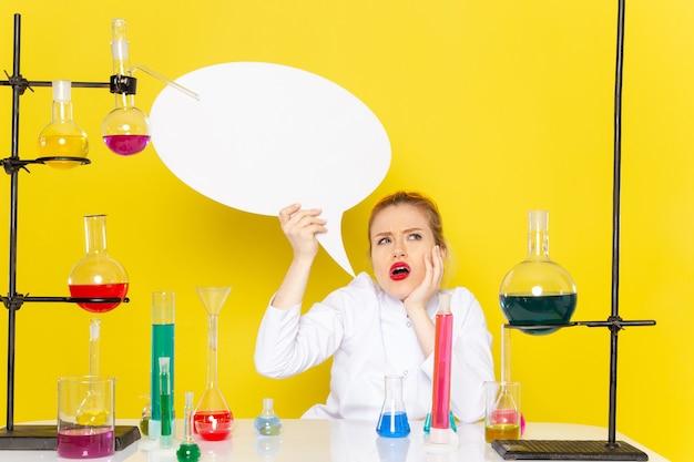 Chimico femminile giovane vista frontale che si siede in vestito bianco con diverse soluzioni che tengono il segno bianco pensando alla scienza chimica dello spazio giallo