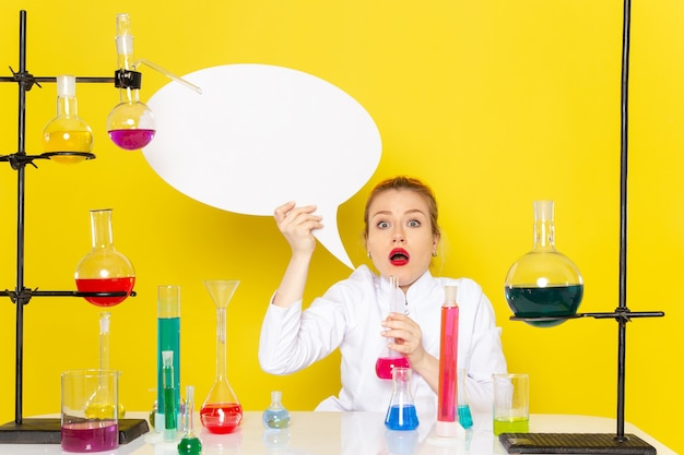 Chimico femminile giovane vista frontale che si siede in vestito bianco con diverse soluzioni che tengono segno bianco sul lavoro di scienza chimica del pavimento giallo