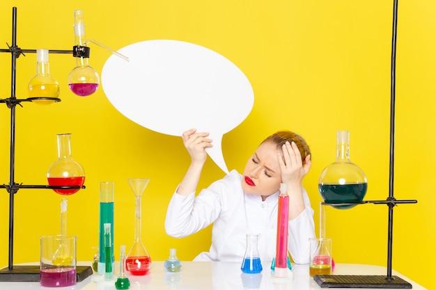 Chimico femminile giovane vista frontale che si siede in vestito bianco con diverse soluzioni che tengono segno bianco sul processo di scienza chimica dello spazio giallo