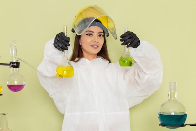 Chimico femminile giovane vista frontale in tuta protettiva speciale che tiene soluzioni colorate sul laboratorio di scienza femminile di chimica chimica lavoro parete verde