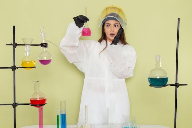 Giovane chimico femminile di vista frontale in boccetta della tenuta del vestito protettivo speciale con la soluzione sul laboratorio di scienza femminile del lavoro di chimica dei prodotti chimici della parete verde