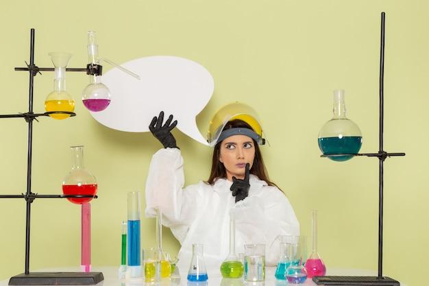 Chimico femminile giovane vista frontale in tuta protettiva speciale che tiene segno bianco sul laboratorio di scienze femminili di chimica chimica muro verde chiaro