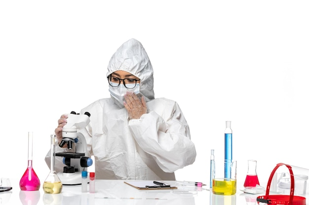 Front view young female chemist in special protective suit using microscope on light white background virus lab covid health chemistry