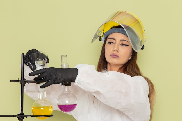 Chimico femminile giovane vista frontale in tuta protettiva speciale che lavora con diverse soluzioni sulla scienza femminile di chimica del laboratorio chimico di lavoro della parete verde
