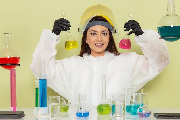 Chimico femminile giovane vista frontale in tuta protettiva speciale che lavora con soluzioni sul laboratorio di scienze femminili di chimica chimica lavoro scrivania verde