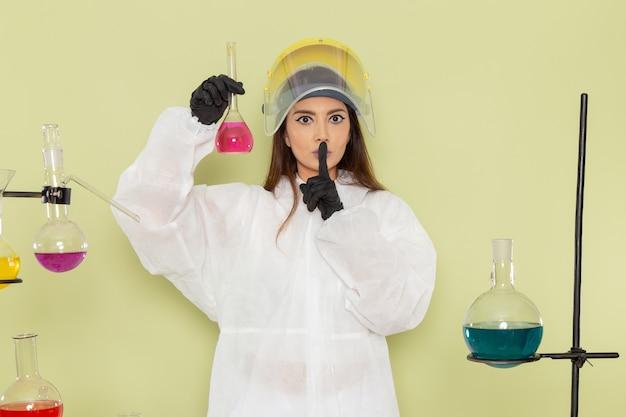 Chimico femminile giovane vista frontale in tuta protettiva speciale che lavora con soluzioni sul laboratorio di scienza femminile di chimica chimica lavoro parete verde