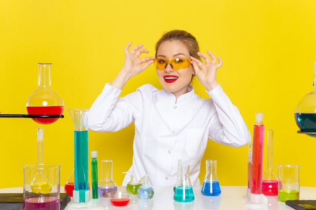 Giovane chimico femminile di vista frontale in vestito bianco davanti al tavolo con soluzioni di ed che si siedono e che sorridono sulla chimica dello spazio giallo