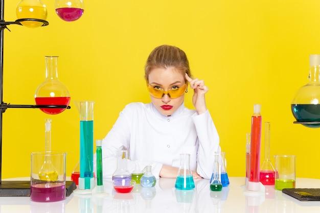 Chimico femminile giovane vista frontale in abito bianco davanti al tavolo con soluzioni ed lavorando con loro mescolando sul lavoro di scienza chimica dello spazio giallo