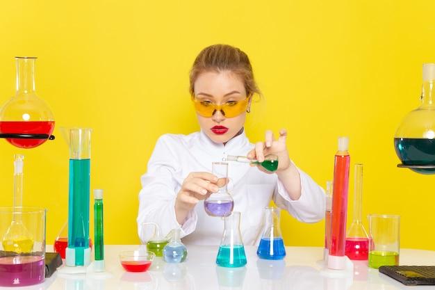 Chimico femminile giovane vista frontale in abito bianco davanti al tavolo con soluzioni ed lavorando con loro mescolando sulla scienza chimica dello spazio giallo
