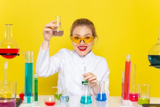 Giovane chimico femminile di vista frontale in vestito bianco davanti al tavolo con soluzioni di ed che lavorano con loro sulla chimica dello spazio giallo