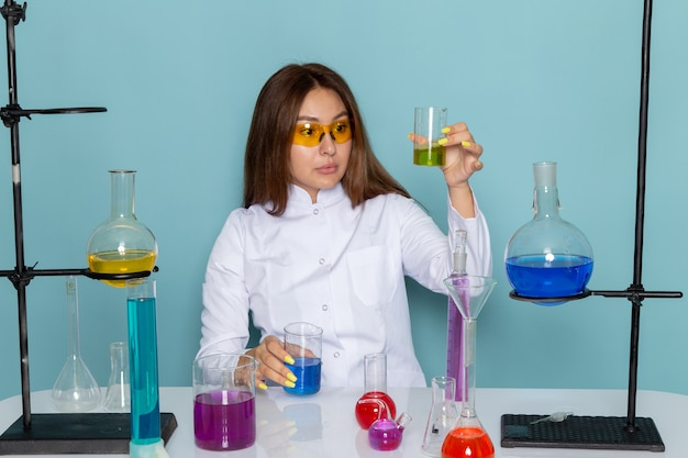 Front view of young female chemist in white suit in front of table working with solutions