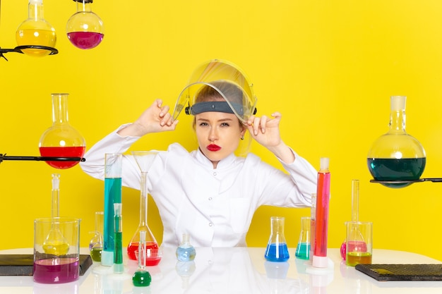 Front view young female chemist in white suit with ed solutions takign off helmet on the yellow space chemistry science s
