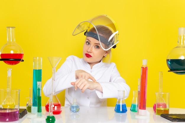 Vista frontale giovane chimico femminile in abito bianco con soluzioni ed che toglie il casco che mostra il tempo sulla scienza chimica dello spazio giallo s