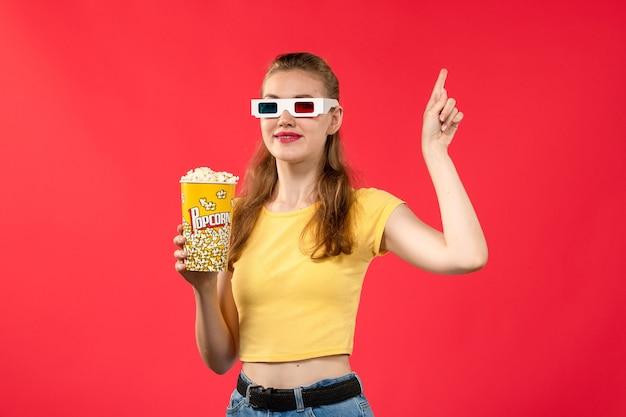 Giovane femmina di vista frontale al cinema che tiene popcorn in occhiali da sole d sul colore femminile del cinema del cinema del cinema della parete rossa