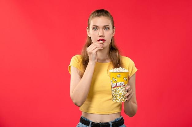 Giovane femmina di vista frontale al cinema che tiene popcorn e che mangia sul film di divertimento femminile del cinema del teatro di film della parete rossa