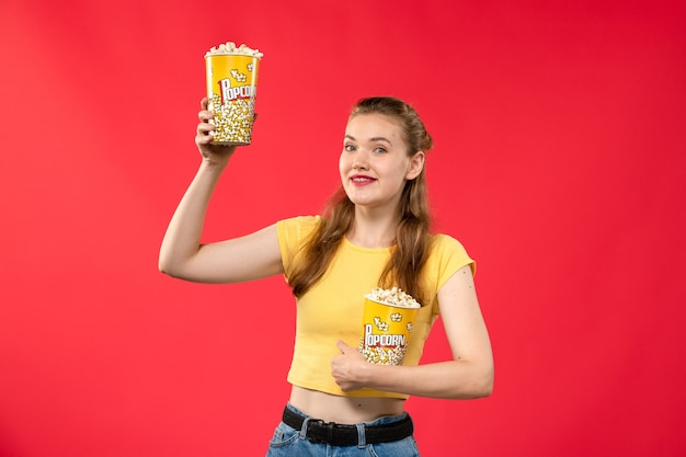 Giovane femmina di vista frontale al cinema che tiene popcorn sul film rosso chiaro del cinema del cinema della parete del cinema del tempo di divertimento femminile