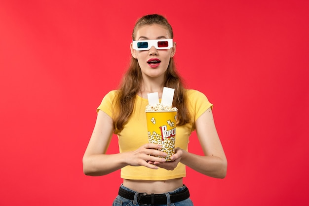 Front view young female at cinema holding popcorn package in -d sunglasses holding tickets on red desk movies theaters cinema film girl