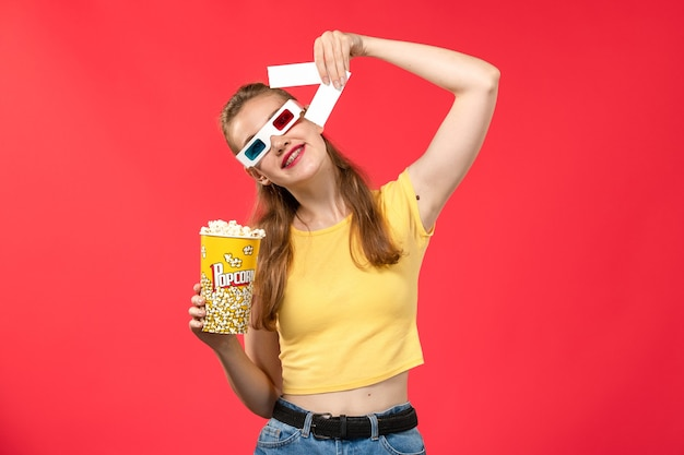Front view young female at cinema holding popcorn package in -d sunglasses holding tickets on red wall movies theaters cinema film girl