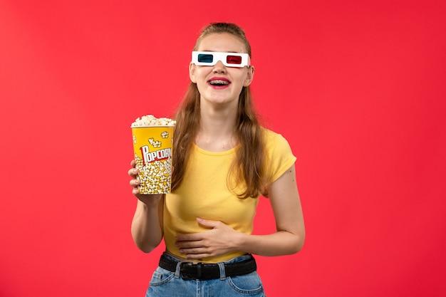 Giovane femmina di vista frontale al cinema che tiene il pacchetto del popcorn in occhiali da sole d sul film di divertimento femminile del cinema del cinema del cinema della parete rossa