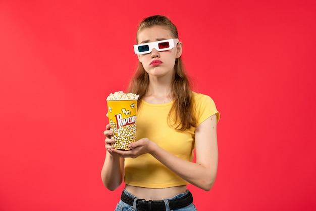 Giovane femmina di vista frontale al cinema che tiene il pacchetto del popcorn in occhiali da sole -d sulla ragazza del film del cinema del cinema di film della parete rossa