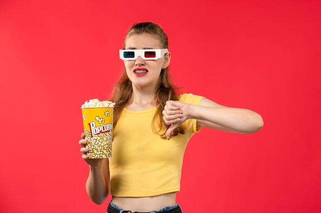 Giovane femmina di vista frontale al cinema che tiene il pacchetto del popcorn in occhiali da sole -d sul film del cinema del teatro di film della parete rossa