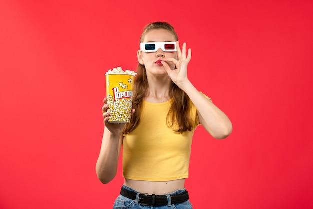 Giovane femmina di vista frontale al cinema che tiene il pacchetto del popcorn in -d occhiali da sole sul film di divertimento del cinema del teatro di film della parete rossa