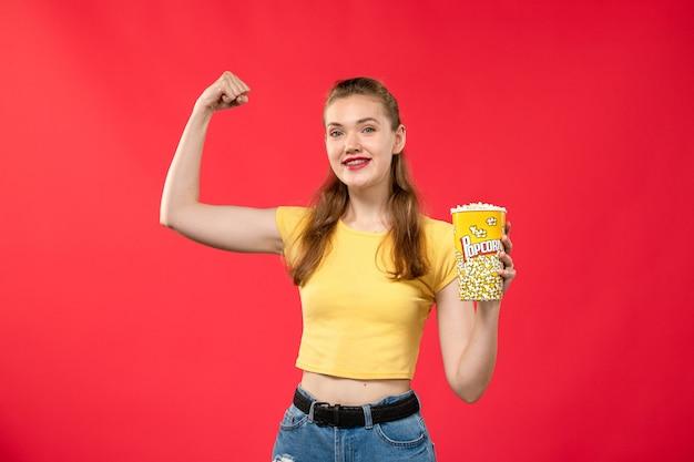 Giovane femmina di vista frontale al cinema che tiene il pacchetto del popcorn e che flette sul film di divertimento femminile dello spuntino del cinema del cinema dei film della parete rossa