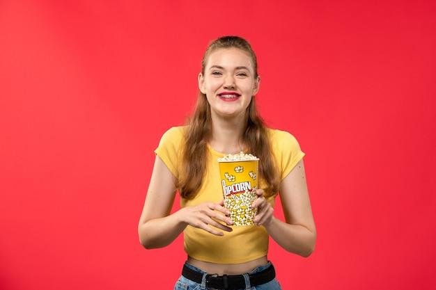 Giovane femmina di vista frontale al cinema che tiene il pacchetto del popcorn e che ride sul film di divertimento del cinema del cinema di film della parete rosso-chiaro