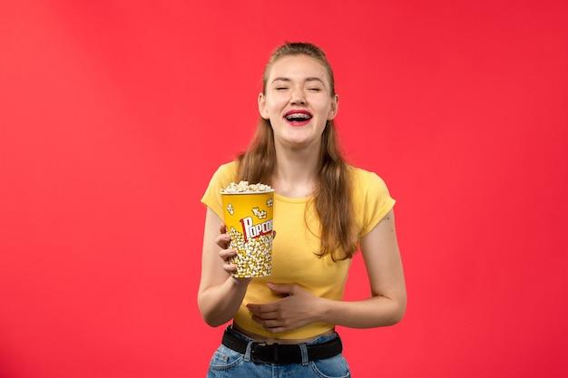 Giovane femmina di vista frontale al cinema che tiene il pacchetto del popcorn e che ride sul film di divertimento femminile del cinema del teatro di film della parete rossa